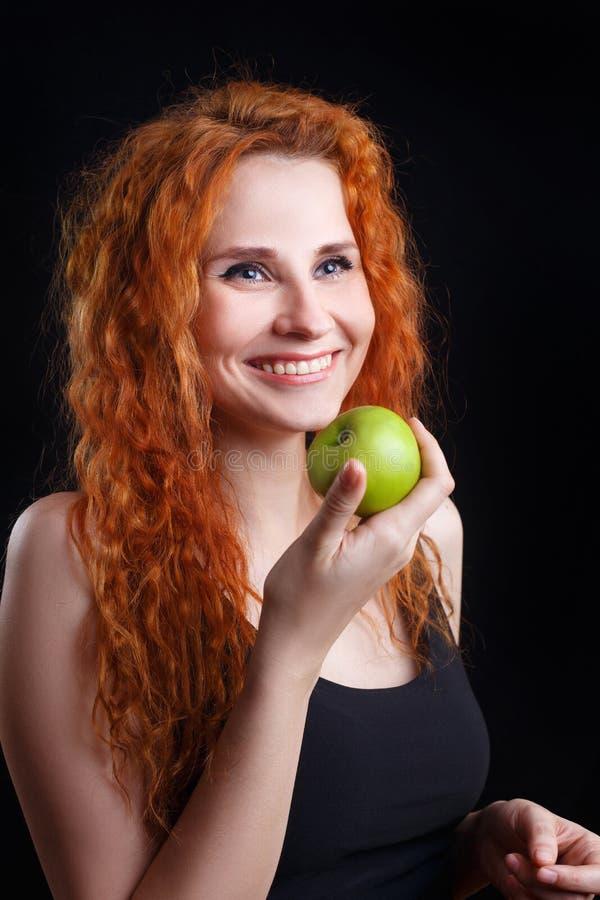 Härlig ung rödhårig mankvinna som ler rymma ett grönt äpple arkivbild