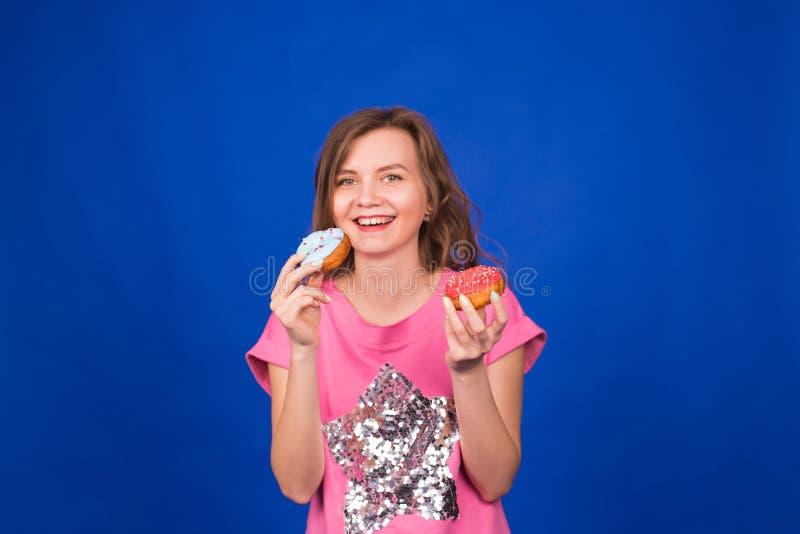Härlig ung rolig flicka med donuts på blå bakgrund Sjukligt banta, skräpmat-, parti- och berömbegreppet fotografering för bildbyråer