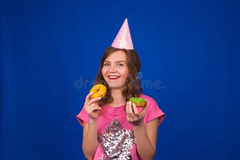 Härlig ung rolig flicka med donuts på blå bakgrund Sjukligt banta, skräpmat-, parti- och berömbegreppet royaltyfri fotografi