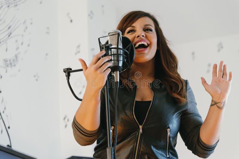 Härlig ung sångare som sjunger i direkt royaltyfri bild