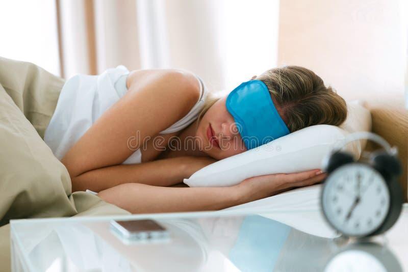 Härlig ung sömnig kvinna med sömnmaskeringen som hemma vilar i säng med ringklockan i sovrum arkivbild