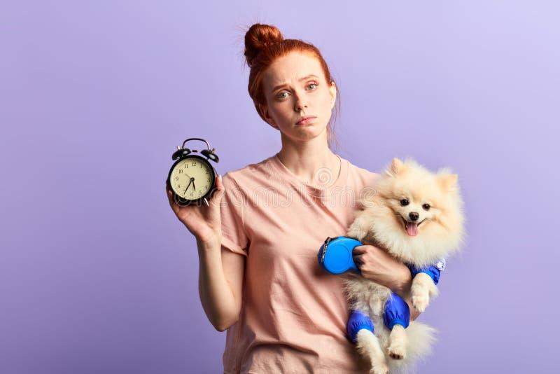 Härlig ung sömnig olycklig kvinna som rymmer en klocka och hennes hund i händer arkivfoto