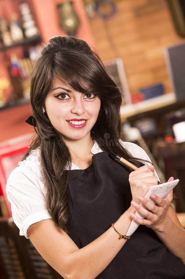 Härlig ung servitris som tar en beställning royaltyfria bilder
