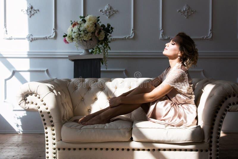 Härlig ung sexig blond kvinna i en siden- ämbetsdräkt som sitter på en soffa som framme kramar hennes ben av ett fönster i stråla arkivfoton