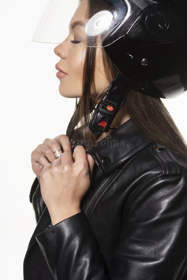 Härlig ung sexig cyklistflicka som bär en bodysuit för svartläderomslag och en hjälm på hennes huvud bakgrund isolerad white royaltyfri fotografi