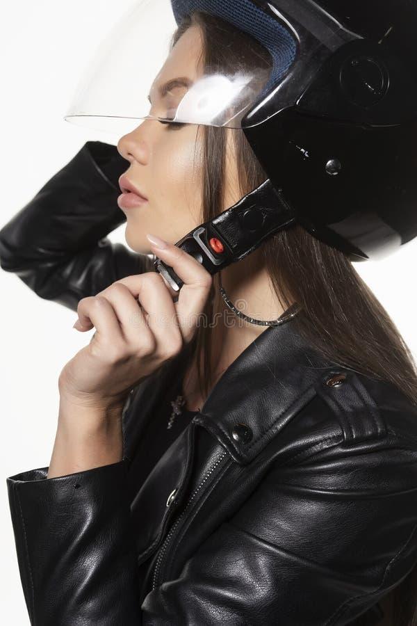 Härlig ung sexig cyklistflicka som bär en bodysuit för svartläderomslag och en hjälm på hennes huvud bakgrund isolerad white arkivbilder