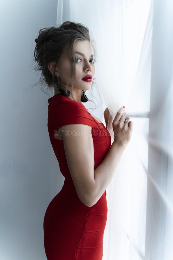 Härlig ung sexig elegant flicka med stora bröst och att bära en röd åtsittande klänning och örhängen som står sensually vid gardi arkivbild