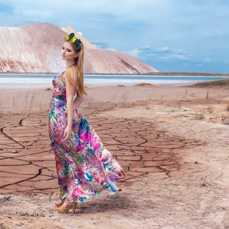 Härlig ung sexig flickamodell med långt rött hår i en härlig krans av blommor och en lång ljus kulör klänning i öknen arkivfoton