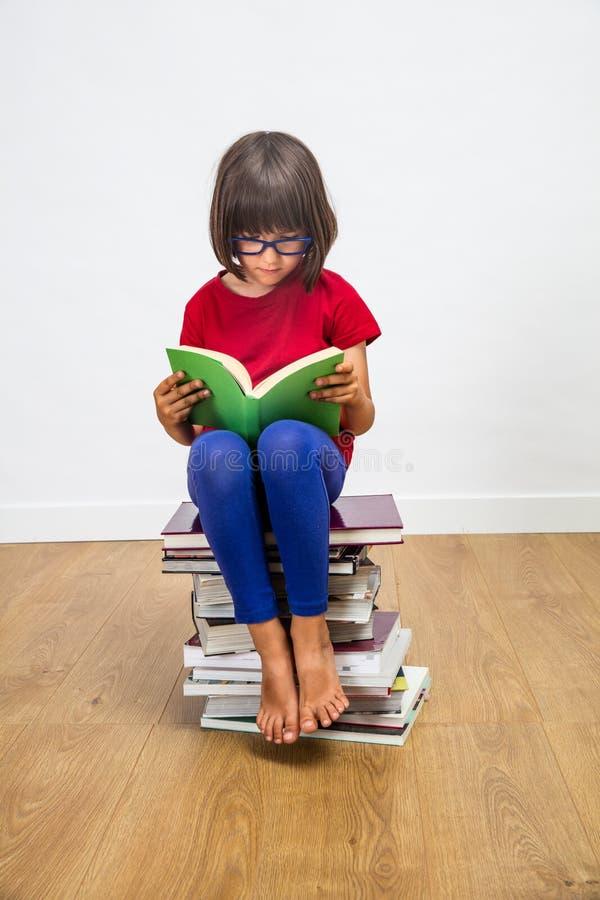 Härlig ung skolflicka med glasögon som läser för kulturmakt, inomhus arkivbilder