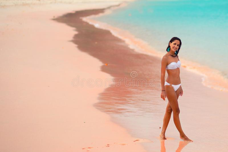 Härlig ung solbränd kvinna i den vita bikinin som poserar på den rosa stranden, ö Lombok, Bali kopiera avst?nd royaltyfri fotografi