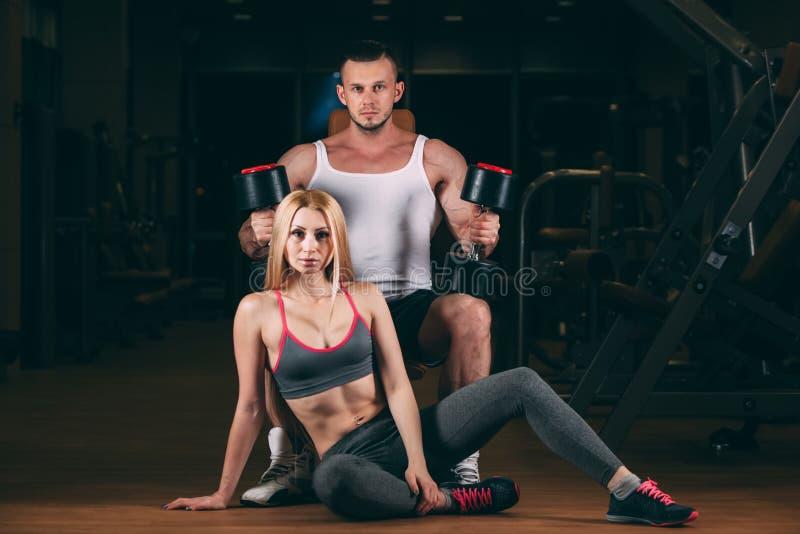 Härlig ung sportig sexig parvisningmuskel och genomkörare i idrottshallhantel arkivfoto