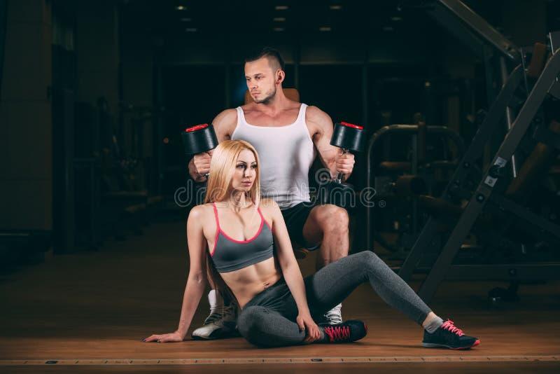 Härlig ung sportig sexig parvisningmuskel och genomkörare i idrottshallhantel fotografering för bildbyråer