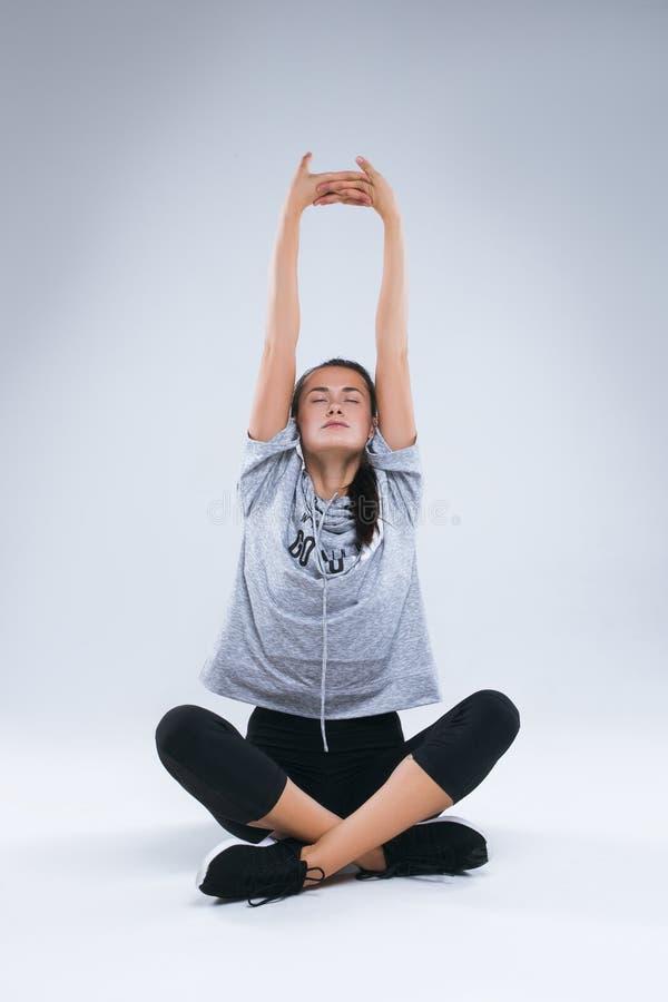 Härlig ung sportkvinna som gör yogaövningar och lyfter upp henne händer royaltyfria foton