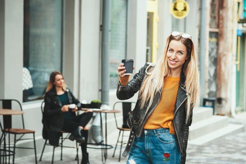 Härlig ung stads- kvinna som bär i stilfull kläder som rymmer kaffekoppen och ler, medan promenera gatan arkivfoton