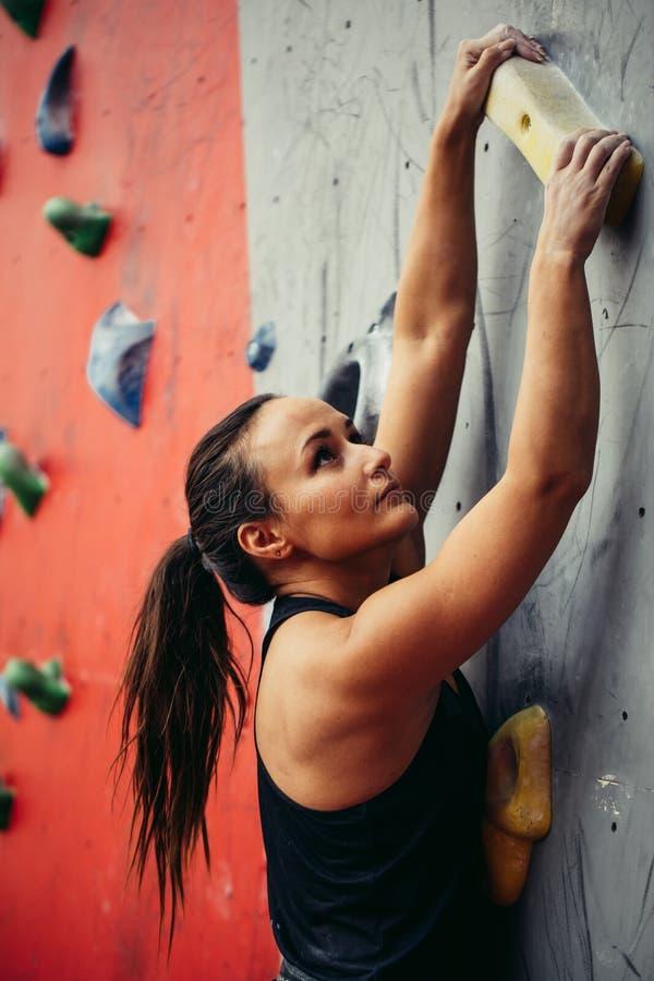 Härlig ung stark kvinnaklättring på bästa sikt för röd konstgjord vägg royaltyfri foto