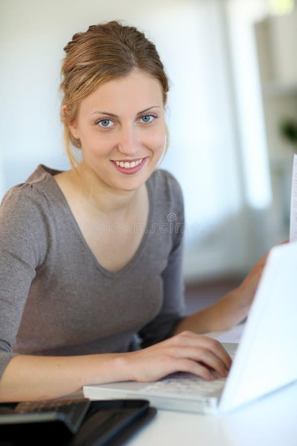 Härlig ung student som arbetar på bärbara datorn arkivfoton