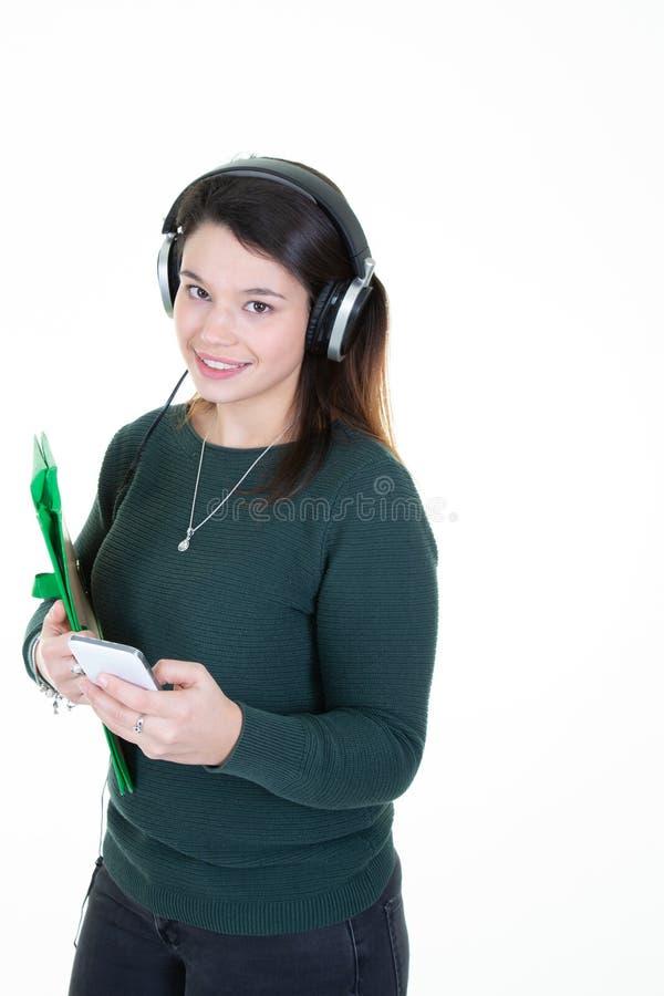 Härlig ung studentkvinna i hörlurar som lyssnar till musik som ler att stå på en vit bakgrund i grön tröja arkivbild