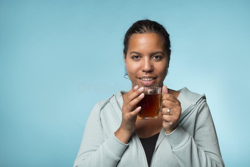 Härlig ung svart kvinna som dricker varmt te på en blå backgrou royaltyfri fotografi