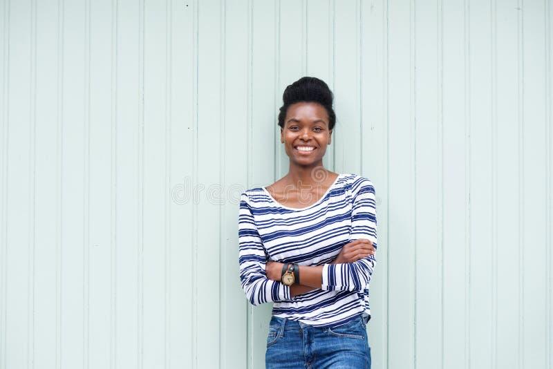 Härlig ung svart kvinna som ler med korsade armar royaltyfri bild