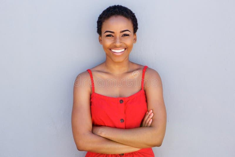 Härlig ung svart kvinna som ler mot den gråa väggen arkivfoto