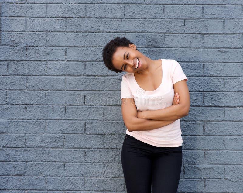 Härlig ung svart kvinna som skrattar mot den gråa väggen arkivbild
