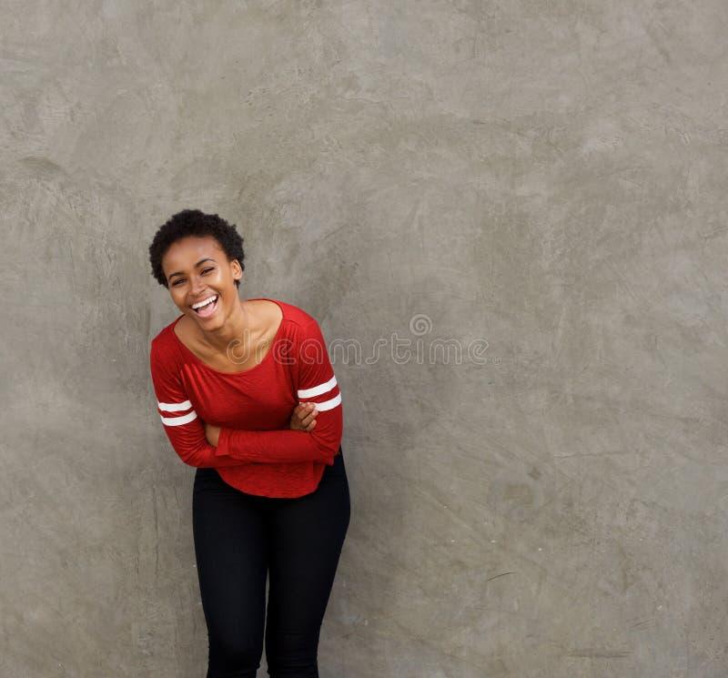 Härlig ung svart kvinnabenägenhet mot väggen och att skratta royaltyfria foton