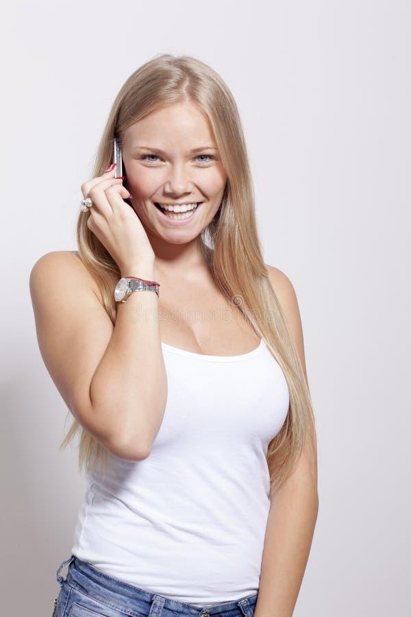 Härlig ung telefon för smartphone för tonåringkvinnahåll med leende fotografering för bildbyråer