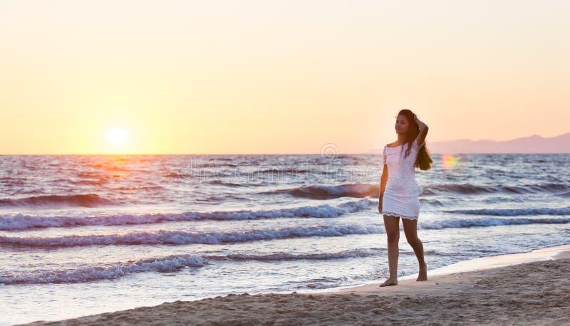 Härlig ung tonåring med en vit klänning på stranden på solar royaltyfria foton