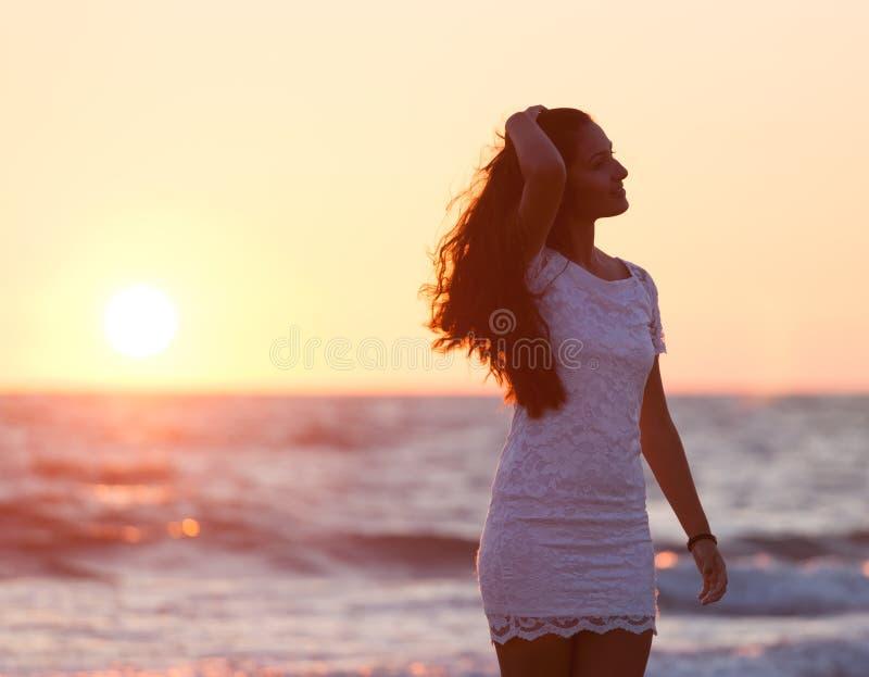 Härlig ung tonåring med en vit klänning på stranden på solar arkivfoto