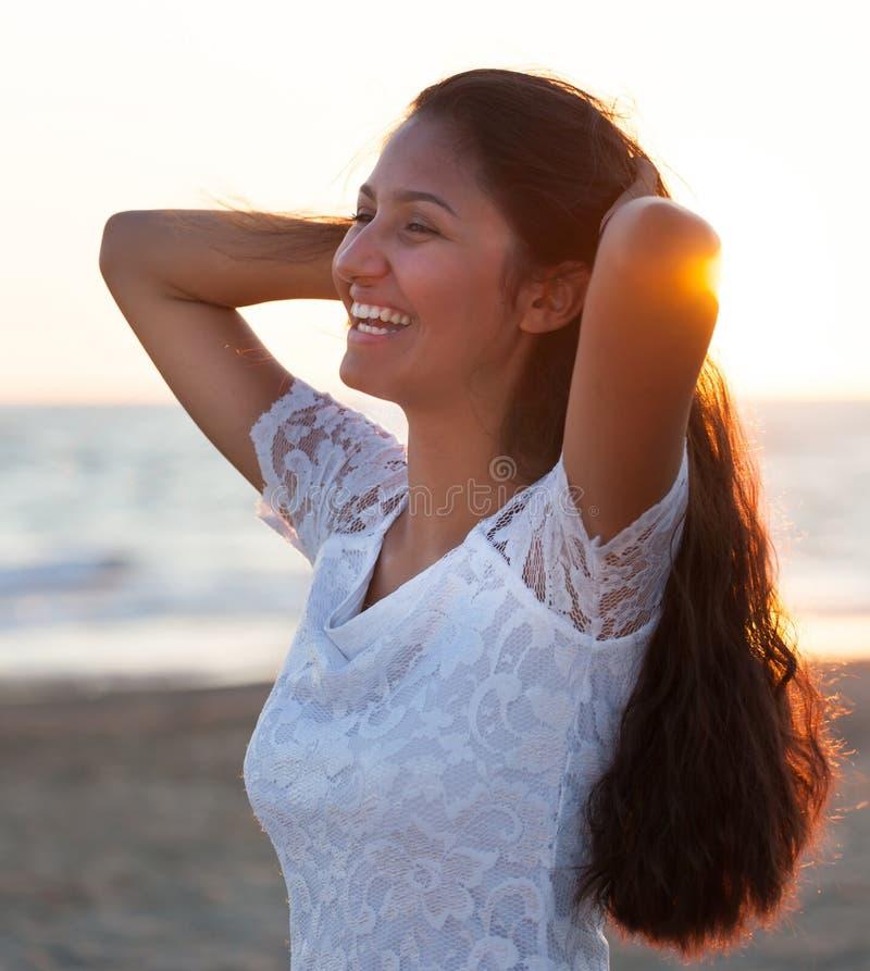 Härlig ung tonåring med en vit klänning på stranden på solar arkivbilder