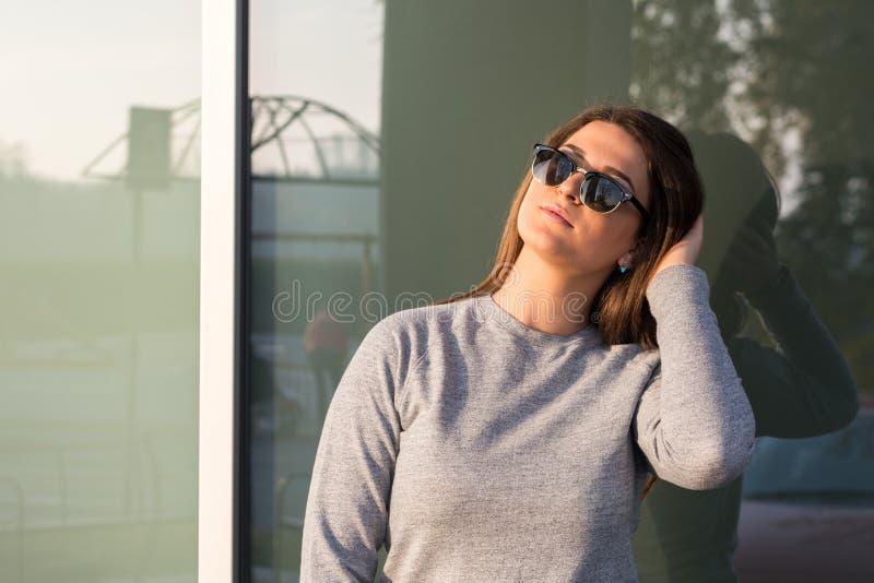 Härlig ung tonårs- le flicka som framme poserar av det glass fönstret royaltyfri fotografi