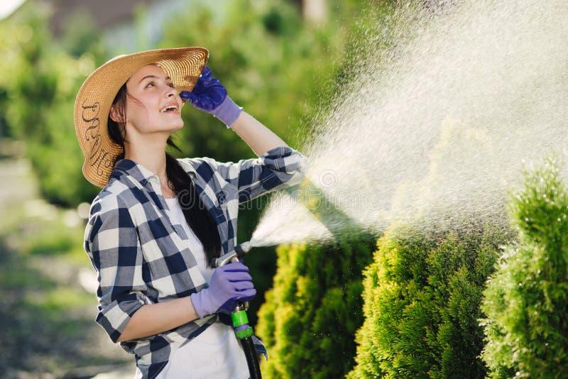 Härlig ung trädgårdsmästarekvinna som bevattnar trädgården i varm sommardag royaltyfri fotografi