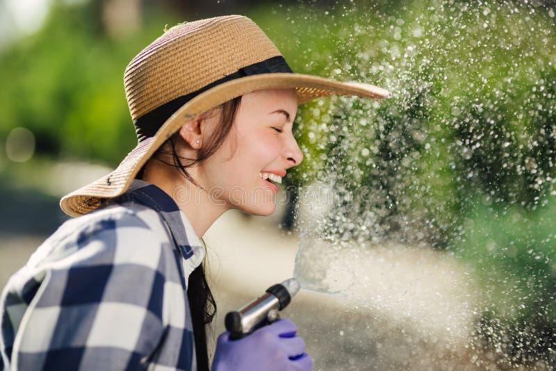 Härlig ung trädgårdsmästarekvinna som har gyckel, medan bevattna trädgården i varm sommardag arkivfoton