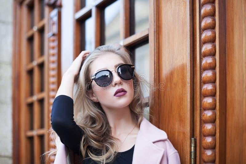 Härlig ung trendig kvinna med solglasögon som ser kameran Kvinnligt dana kvinna för closeupframsidastående fotografering för bildbyråer