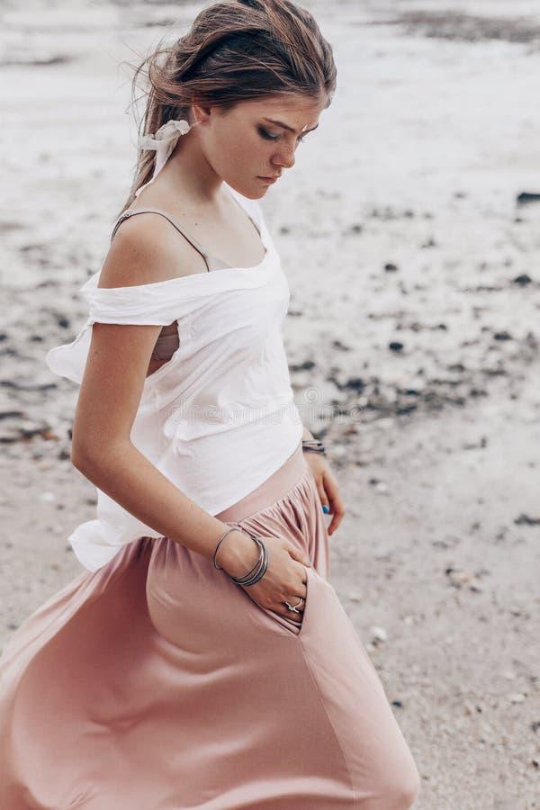 Härlig ung trendig kvinna som går vid kustlinjen arkivbilder
