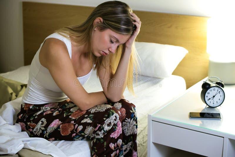 Härlig ung utmattad kvinna som lider sömnlöshet som hemma sitter på säng i sovrummet royaltyfri bild