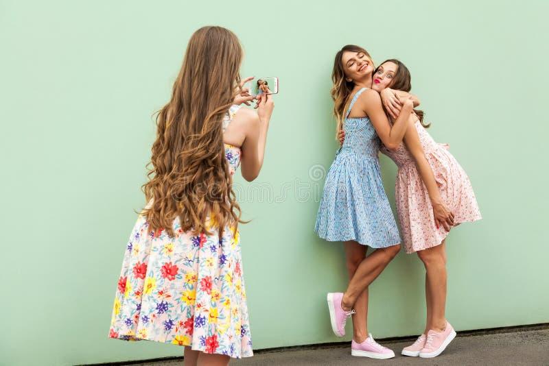 Härlig ung vuxen flicka som tre tar fotoet med en smart telefon royaltyfri fotografi