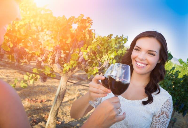 Härlig ung vuxen kvinna som tycker om exponeringsglas av rostat bröd för vinavsmakning i vingården med vänner royaltyfri bild
