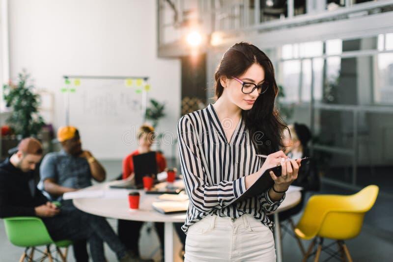 Härlig ung yrkesmässig Caucasian kvinna i regeringsställning med glasögon, säkert uttryck, innehavpennan och legitimationshandlin arkivbilder
