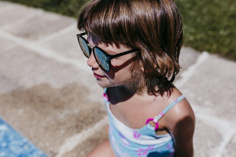 Härlig ungeflicka på pölen som bär modern solglasögon Roligt utomhus Sommartid- och livsstilbegrepp arkivfoto