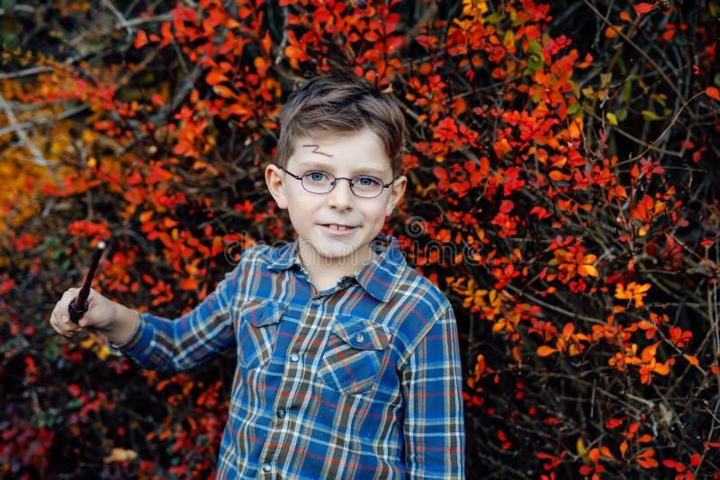 Härlig ungepojke i dräkt som en trollkarl Lyckligt sunt barn som firar allhelgonaafton Pojke med exponeringsglas utomhus på royaltyfri foto