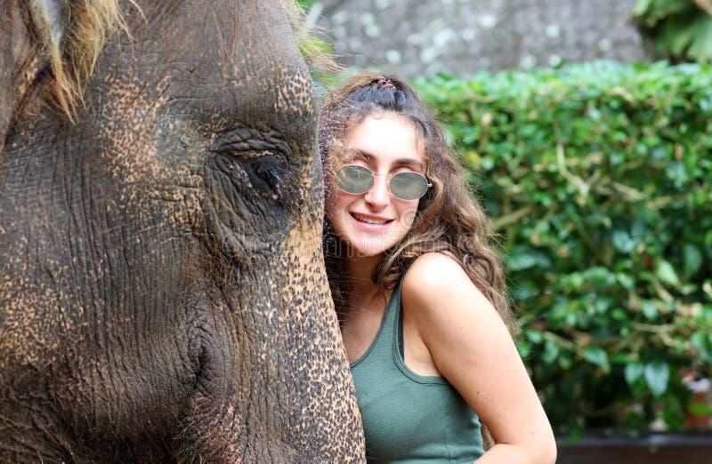 Härlig unik elefant med flickan på en elefantbeskyddreservation i Bali Indonesien fotografering för bildbyråer