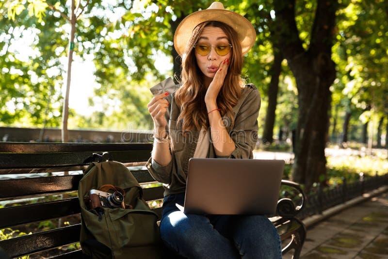 Härlig upphetsad lycklig kvinna som sitter utomhus genom att använda kreditkorten för innehav för bärbar datordator royaltyfri fotografi