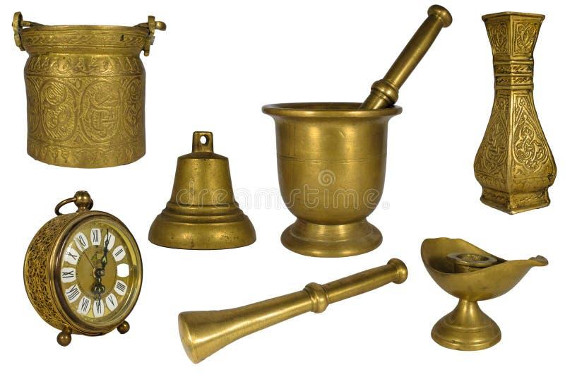 Härlig uppsättning eller samling av tappningmässing eller guld- dekorativa husobjekt som isoleras på vit: klocka mortelstöt, mort arkivfoto