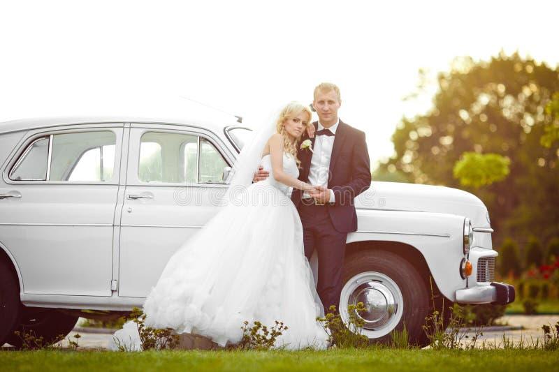 Härlig ursnygg blond brud och stilfull brudgum på backgroen royaltyfria bilder