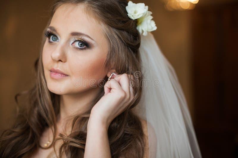 Härlig ursnygg brunettbrud som in sätter på lyxiga örhängen royaltyfria bilder