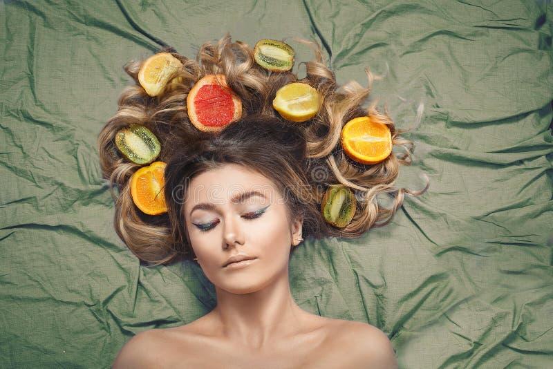 Härlig ursnygg modellflicka med färgrika citrusa sunda frukter i hennes skinande hår Omsorg och hårprodukter Begrepp för håromsor royaltyfri fotografi