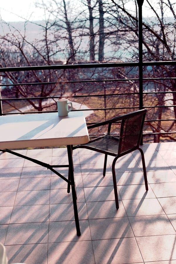 Härlig utomhus- uteplats med stol och tabellen Rottingstol på t royaltyfri bild