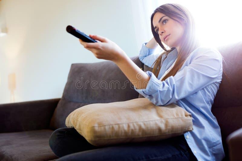 Härlig uttråkad hållande ögonen på TV för ung kvinna och innehavfjärrkontroll hemma royaltyfri bild