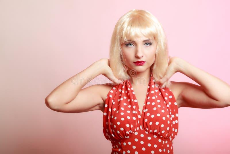 Härlig utvikningsbrudflicka för stående i retro röd klänning för blond peruk. Tappning. arkivfoto